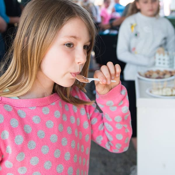 Girl wearing a pink and gray polka dotted sweater tasting NLK's chocolate gelato